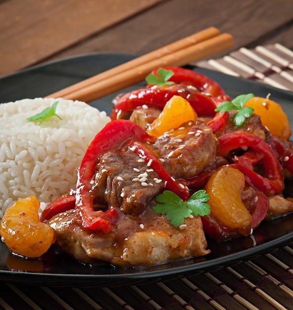 Carne en salsa picante, pimiento dulce y mandarinas con guarnición de arroz hervido Foto Premium