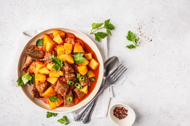 La carne de vaca picante guisó con las patatas en salsa de tomate en la placa blanca, visión superior. Foto Premium