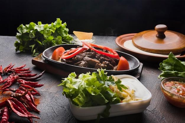 Carne, verduras y aperitivo en mesa de madera. Foto gratis