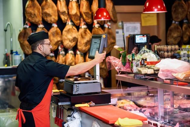 Carnicero en una carnicería pesando la carne y cargando. Foto Premium