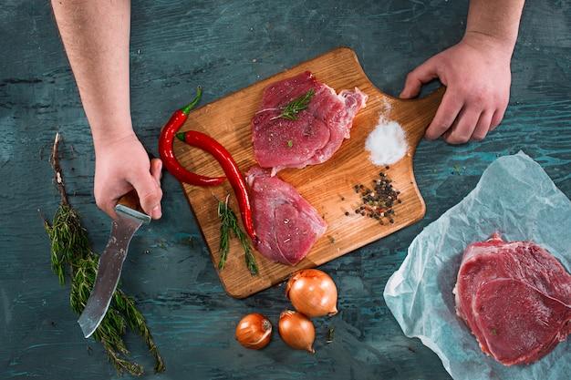 Carnicero cortando carne de cerdo en la cocina Foto gratis