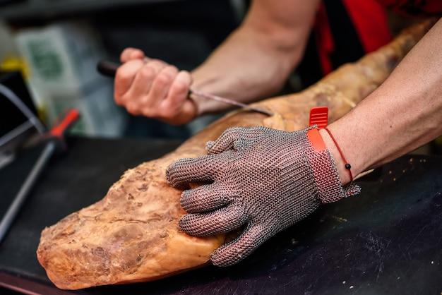 Carnicero deshuesando un jamón con malla metálica de seguridad. Foto gratis