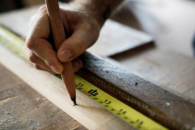 Carpenter con lápiz y cinta de medición en madera Foto gratis