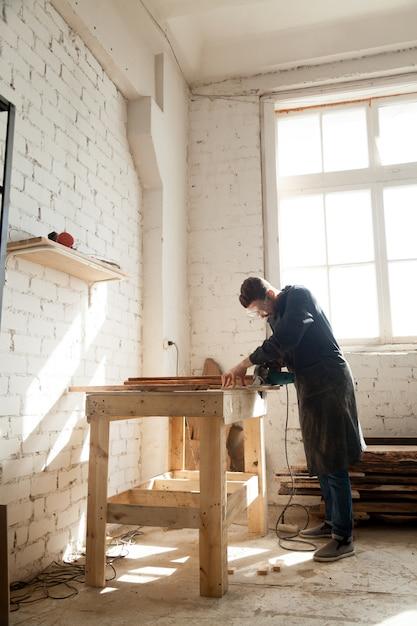 Carpintero con sierra de mano de poder cortar tablones de - Sierra de mano para madera ...