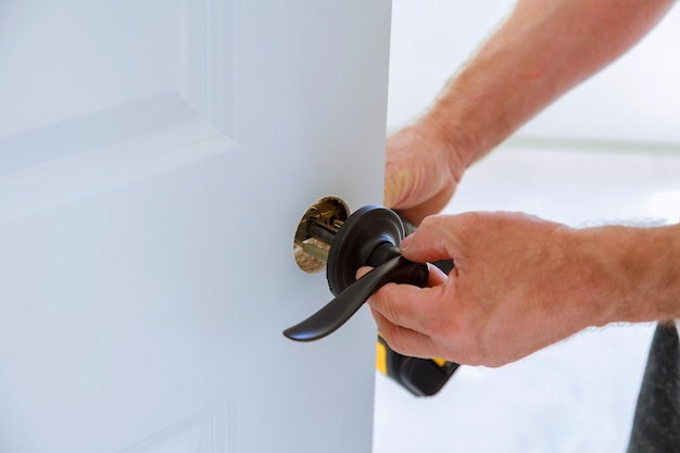 Carpintero instalación de la cerradura de la puerta. Foto Premium
