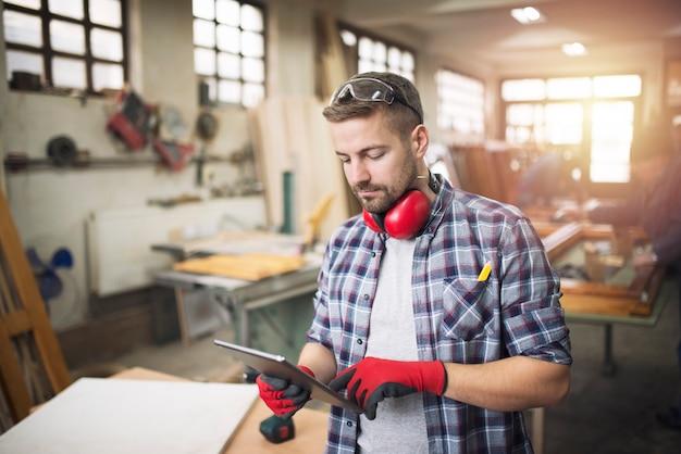 Carpintero joven trabajador profesional con gafas protectoras sosteniendo una tableta y comprobando el diseño de su proyecto en el taller