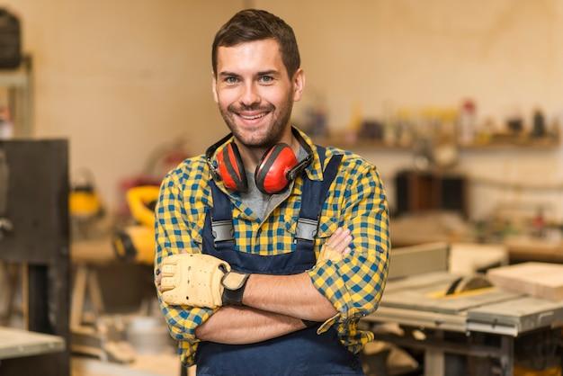 Carpintero de sexo masculino sonriente que se coloca en taller Foto gratis