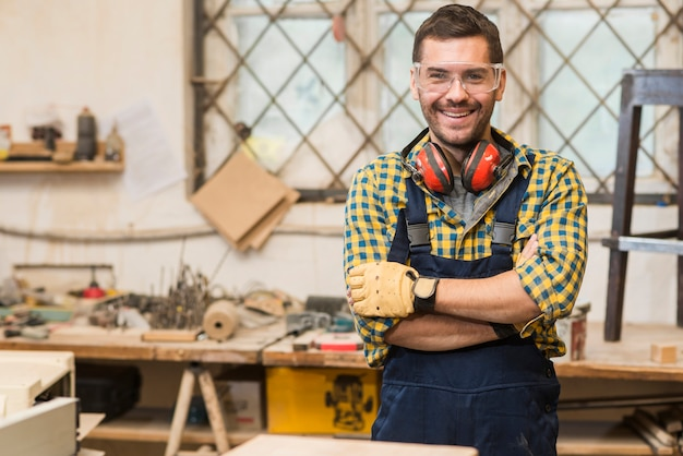Carpintero de sexo masculino sonriente que lleva las gafas de seguridad que se colocan delante de la mesa de trabajo con su brazo cruzado Foto gratis