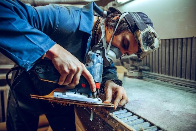 Carpintero con sierra circular para cortar tablas de madera. detalles de construcción de trabajador masculino o hombre práctico con herramientas eléctricas Foto gratis