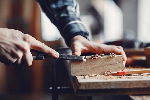 El carpintero trabaja con un arbol. Foto gratis
