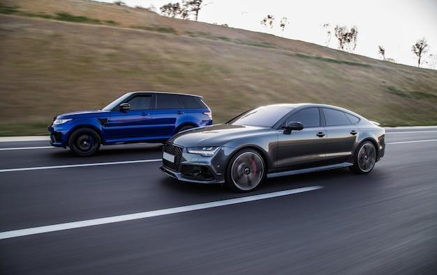 Las carreras de autos de un jeep azul y un sedán gris deportivo. Foto gratis