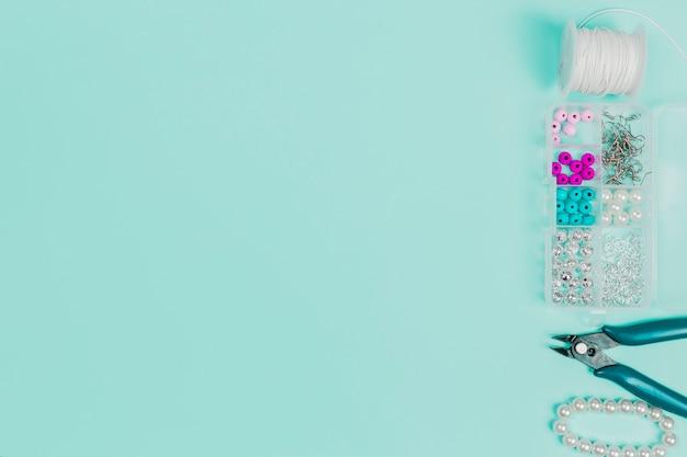 Carrete de hilo; caja de perlas; alicates y brazalete sobre fondo verde azulado con copia espacio para escribir el texto Foto gratis