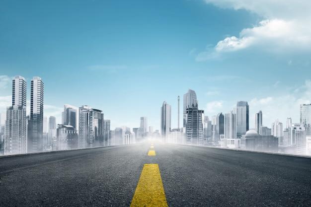 Carretera asfaltada vacía hacia ciudad moderna. Foto Premium