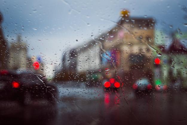 Carretera de la ciudad vista a través de gotas de lluvia en el parabrisas del coche Foto Premium