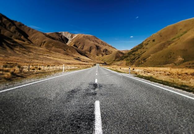 Carretera continua en un paisaje escénico con cordilleras lejos. Foto gratis