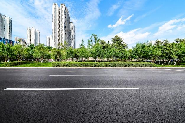 Carretera con un fondo de edificios y parque Foto gratis
