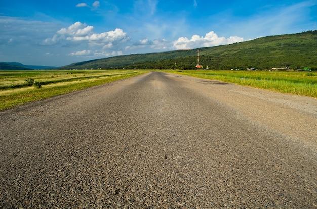 Carretera nacional hermosa y cielo azul entre el campo rural. Foto Premium