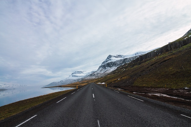 Carretera rodeada por el río y colinas cubiertas de nieve y hierba bajo un cielo nublado en islandia Foto gratis