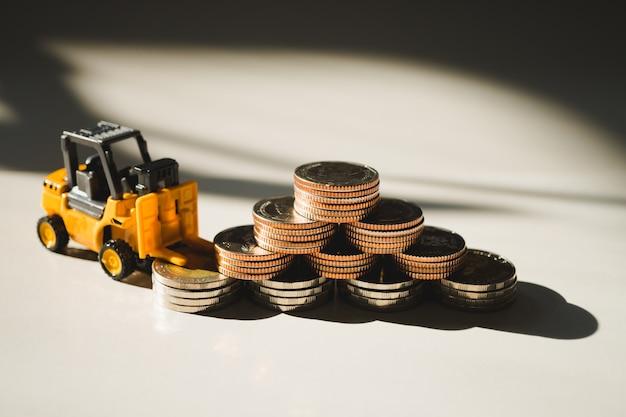 Carretilla elevadora miniatura que trabaja con pila de monedas. Foto Premium