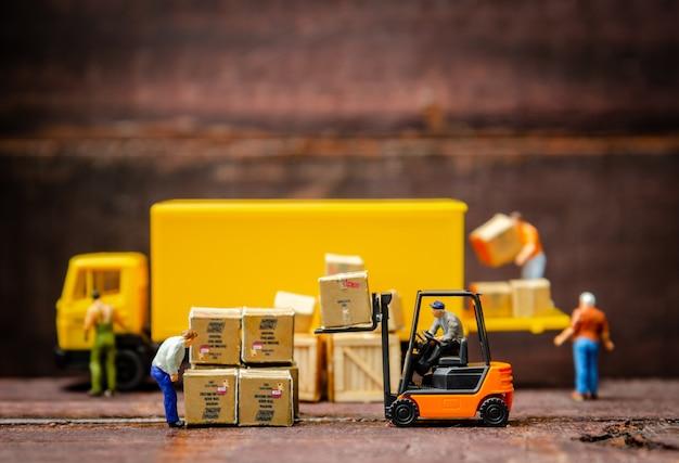 Carretilla elevadora de los trabajadores del almacén miniatura que lleva la caja de las mercancías a semi el camión con el remolque Foto Premium