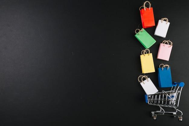 Carrito de compras de juguete con paquetes de colores. Foto gratis