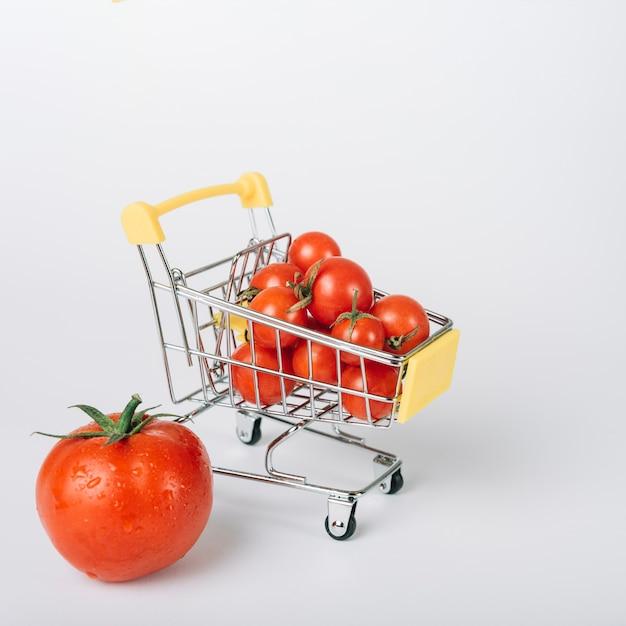 Carrito de compras lleno de tomates rojos frescos sobre fondo blanco Foto gratis