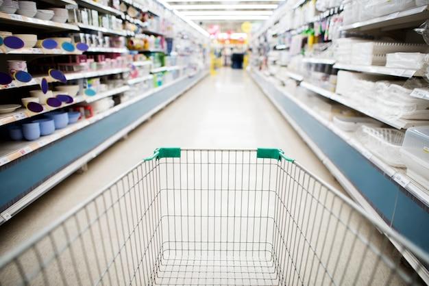 Carrito de compras en el pasillo del supermercado Foto gratis