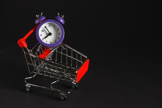 Carrito de compras con reloj despertador. Foto gratis