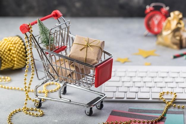 Carrito de compras rojo pequeño con teclado para compras en línea por internet concepto regalos de navidad Foto Premium