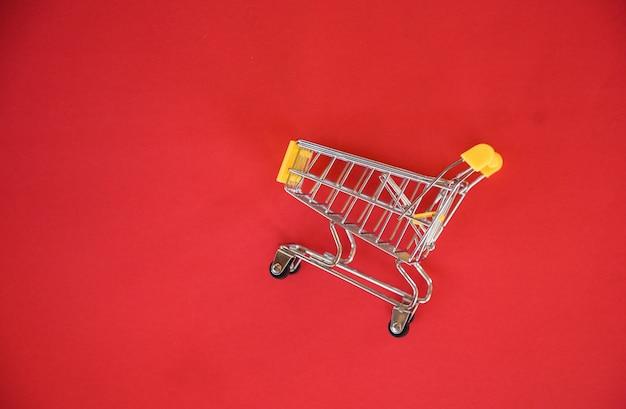 Carrito de compras sobre fondo rojo / concepto de compras en línea con amarillo carrito de compras en vista superior - vacaciones de compras Foto Premium