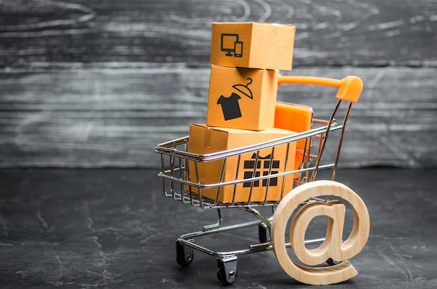 Carrito de supermercado con cajas, mercancía: el concepto de compra y venta de productos. Foto Premium
