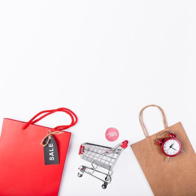 Carro de compras entre bolsas de papel Foto gratis