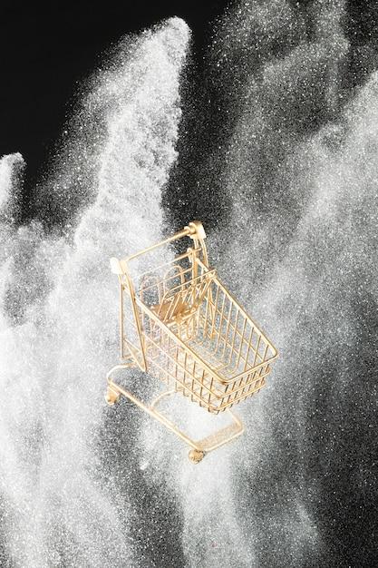 Carro de compras dorado en brillo blanco Foto gratis