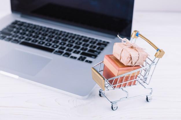 Carro pequeño de supermercado con cajas de regalo y laptop. Foto gratis