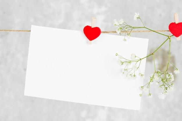 La carta de amor cuelga de una cuerda y una flor sobre un fondo claro. Foto Premium