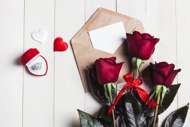 Carta de amor del sobre del día de san valentín con el anillo de compromiso de tarjeta de felicitación Foto gratis