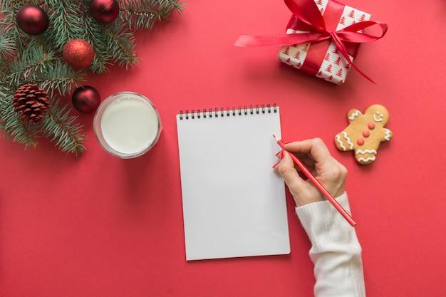 Carta de navidad para santa claus con leche, galletas, pan de jengibre en rojo. vista superior y espacio para su texto. endecha plana. Foto Premium