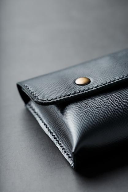 Cartera negra hecha de cuero genuino en oscuro Foto Premium