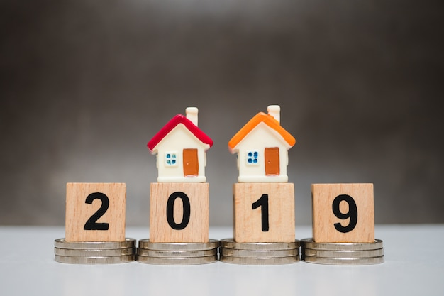 Casa colorida en miniatura en el año 2019 del bloque de madera y monedas de la pila usando como concepto de negocio Foto Premium