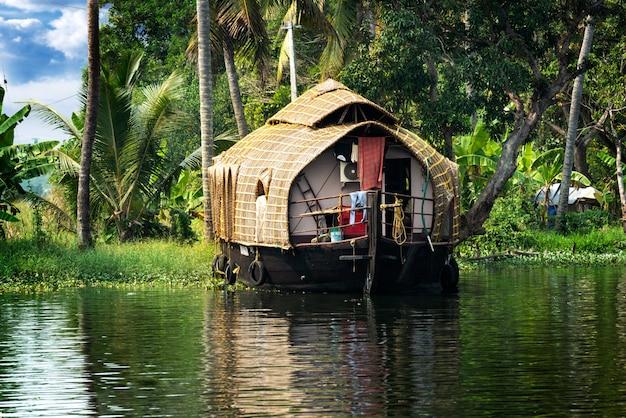 La casa flotante tradicional está anclada a orillas de un lago de pescadores en la india. Foto Premium