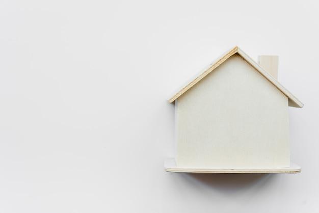 Casa de madera en miniatura simple contra el fondo blanco Foto gratis