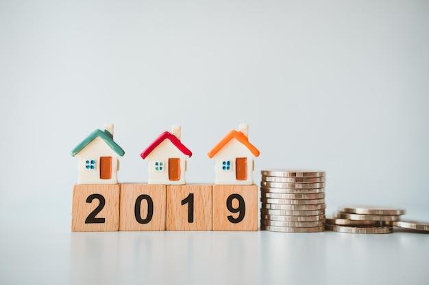 Casa en miniatura en el bloque de madera año 2019 con monedas de pila usando como concepto de negocio y propiedad Foto Premium