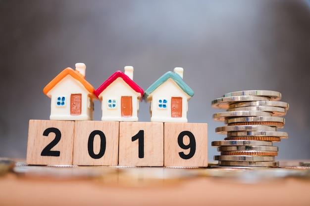 Casa en miniatura en el bloque de madera año 2019 con pila de monedas usando como concepto de negocio y propiedad Foto Premium