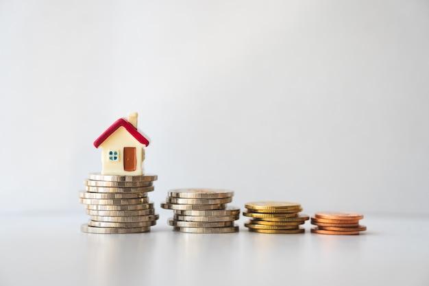 Casa miniatura en monedas de pila usando como concepto de propiedad y negocio Foto Premium