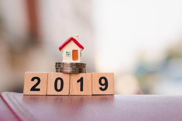 Casa miniatura en la pila de monedas y bloque de madera año 2019 utilizando como concepto de negocio y propiedad Foto Premium