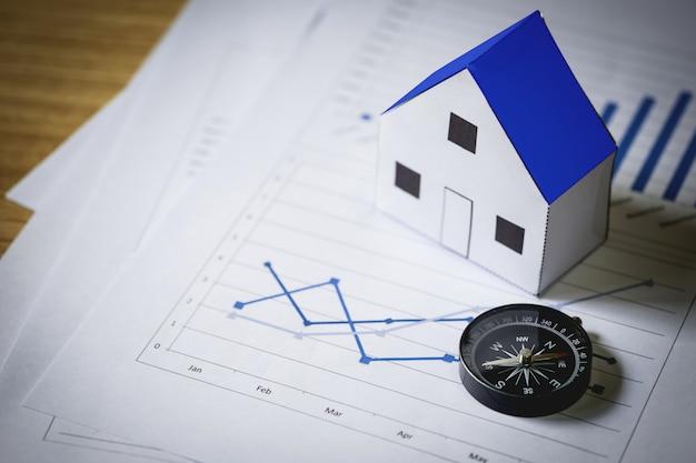 Casa modelo y brújula en el fondo del plan, concepto de bienes raíces Foto gratis