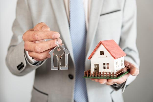 Casa modelo de juguete y llaves en manos de una persona de negocios Foto gratis