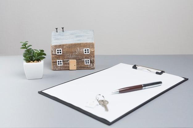 Casa modelo y llaves con portapapeles sobre superficie gris. Foto Premium