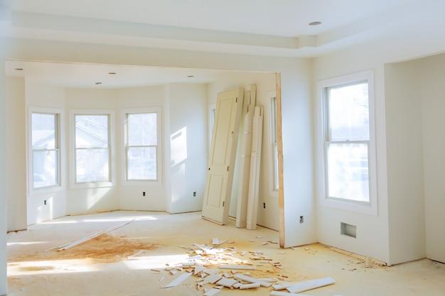 Casa nueva de construcción interior con pisos de madera sin terminar y armarios gemelos. Foto Premium