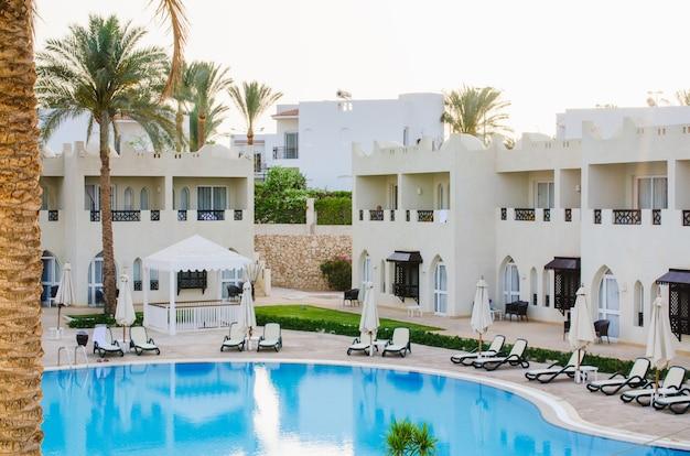 Casas blancas y piscina en territorio de hotel de cinco estrellas en sharm el sheikh. Foto Premium